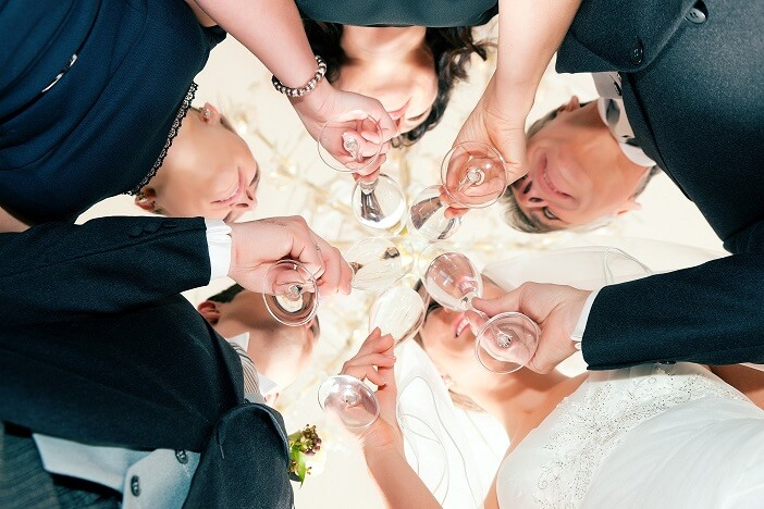 Wedding party bride, groom and bride father clinking glasses with sparkling wine standing under a luster - close-up